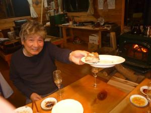 小川山荘での三村さん。奥様が差し入れてくださったのどぐろの頭を差し出す。2010年9月25日、西浦さん還暦祝いにて。
